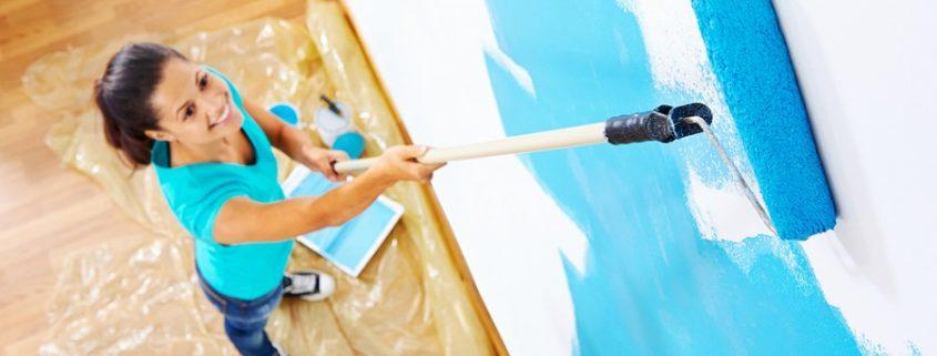 Frau bringt blaue Wandbeschichtung mit Farbrolle an der Wand an